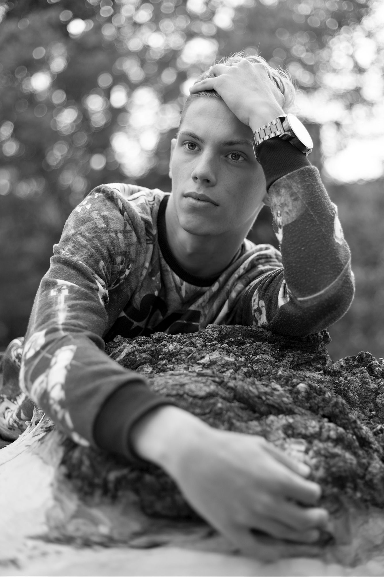Portrait eines jungen Mannes, der auf einem Baumstamm liegt. Das Spiel mit Schärfe und Unschärfe.
