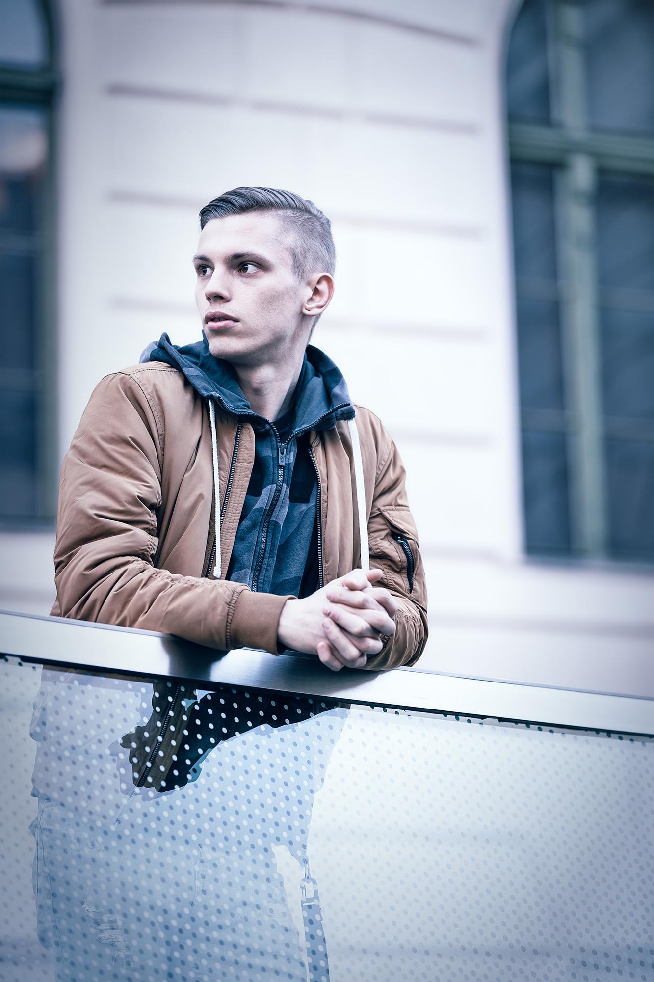 Junger Mann im Joanneumsviertel in Graz, der sich an ein Metallgeländer lehnt und nach links blinkt.