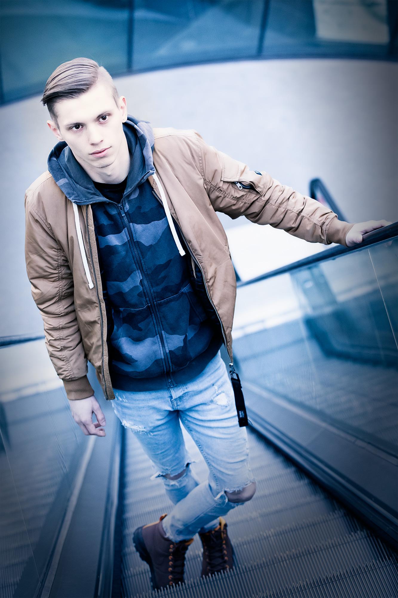 Junger Mann im Joanneumsviertel in Graz, der sich an eine Rolltreppe lehnt und nach oben blickt.