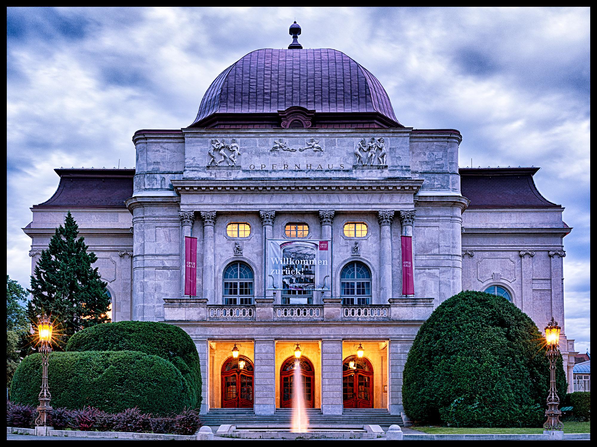 Eine Frontalansicht der Grazer Oper vom Opernring in der blauen Stunde
